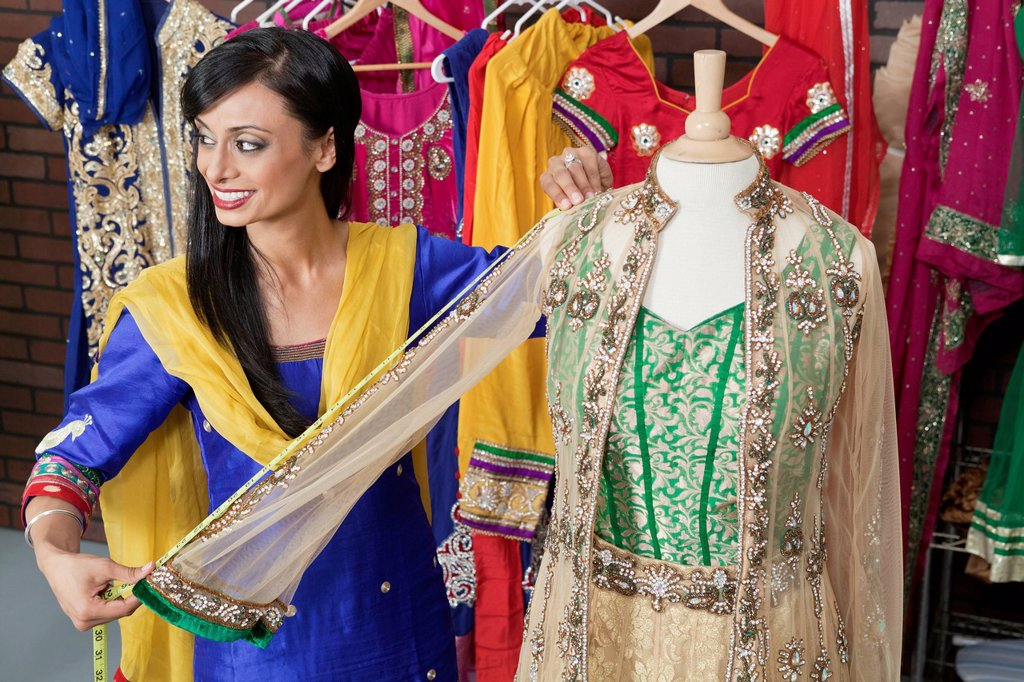 Indian female dressmaker measuring traditional outfit at design studio : Stock Photo