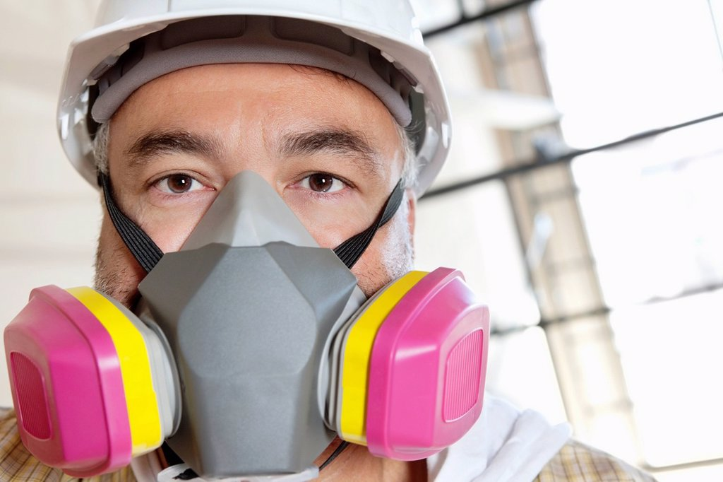 Stock Photo: 1654R-52516 Portrait of male worker wearing dust mask at construction site