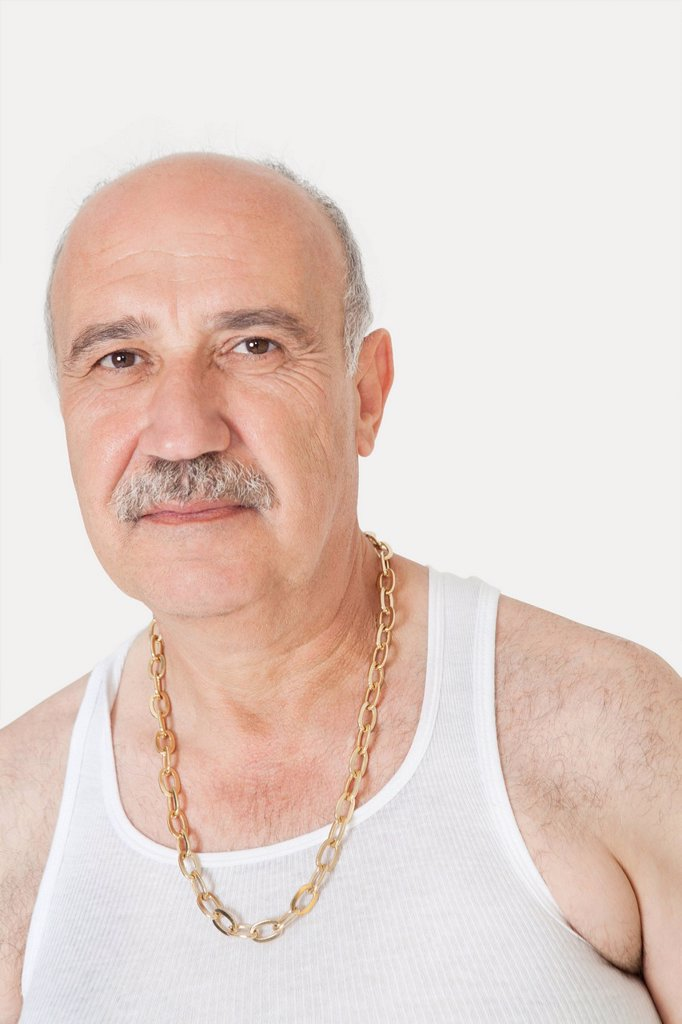 Stock Photo: 1654R-52555 Portrait of senior man in vest with gold chain over gray background