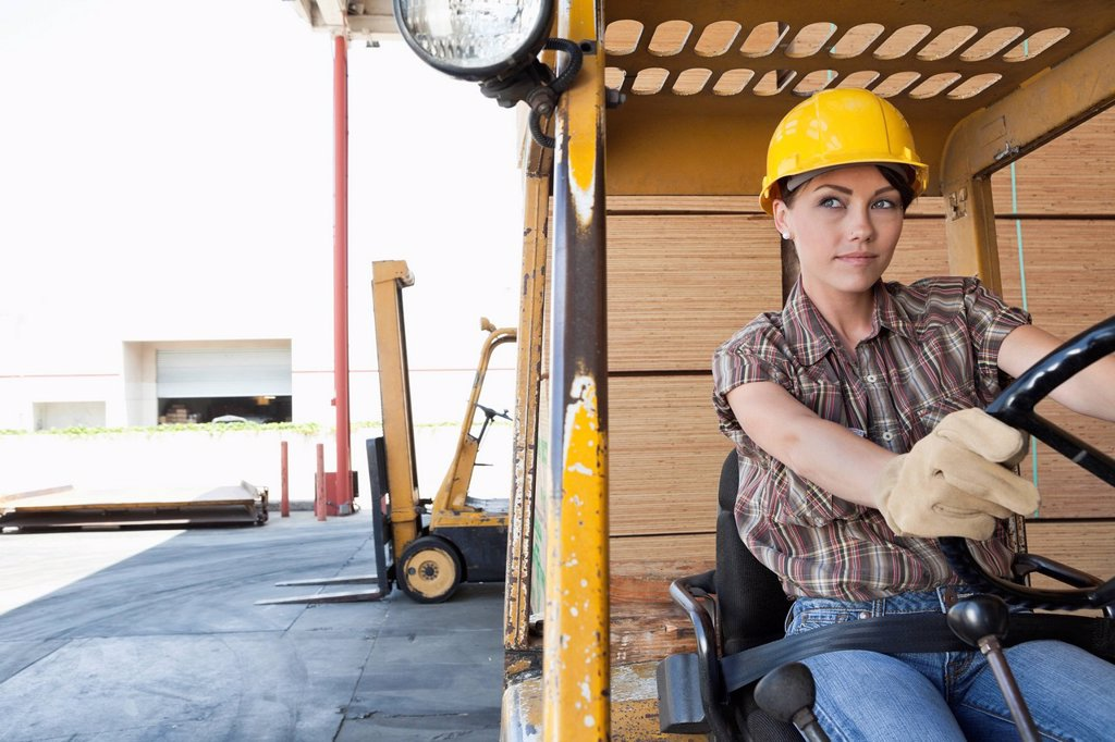 Female industrial worker driving forklift truck : Stock Photo