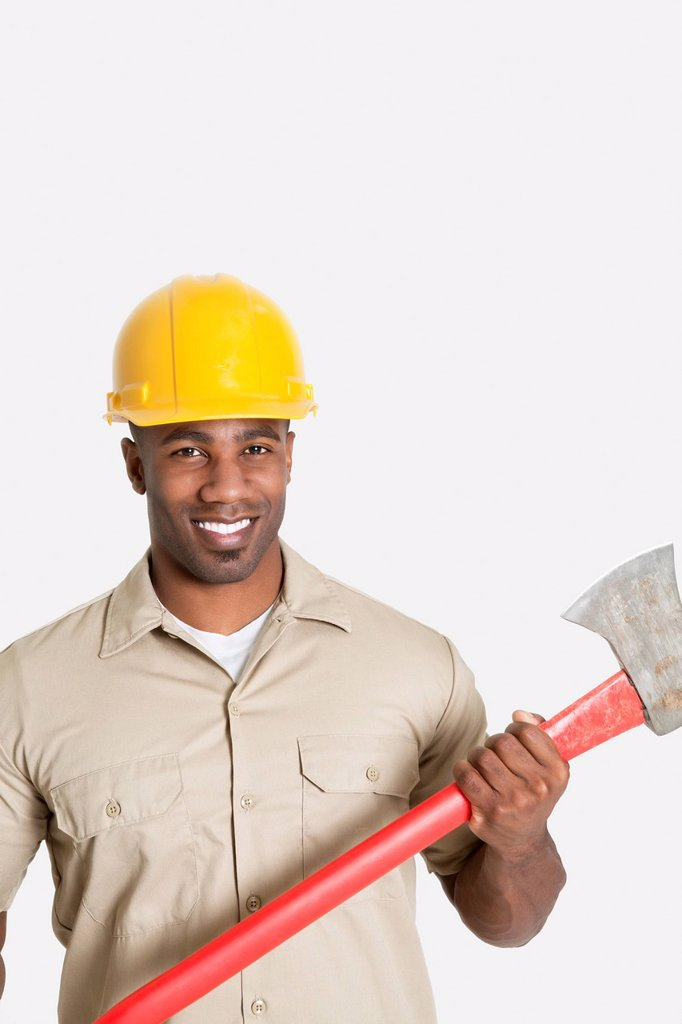 Stock Photo: 1654R-52625 Portrait of happy African male construction worker holding axe over gray background