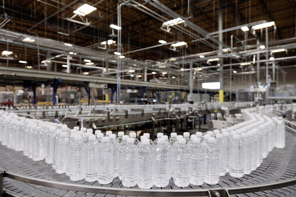 Bottled water on conveyor at bottling plant : Stock Photo