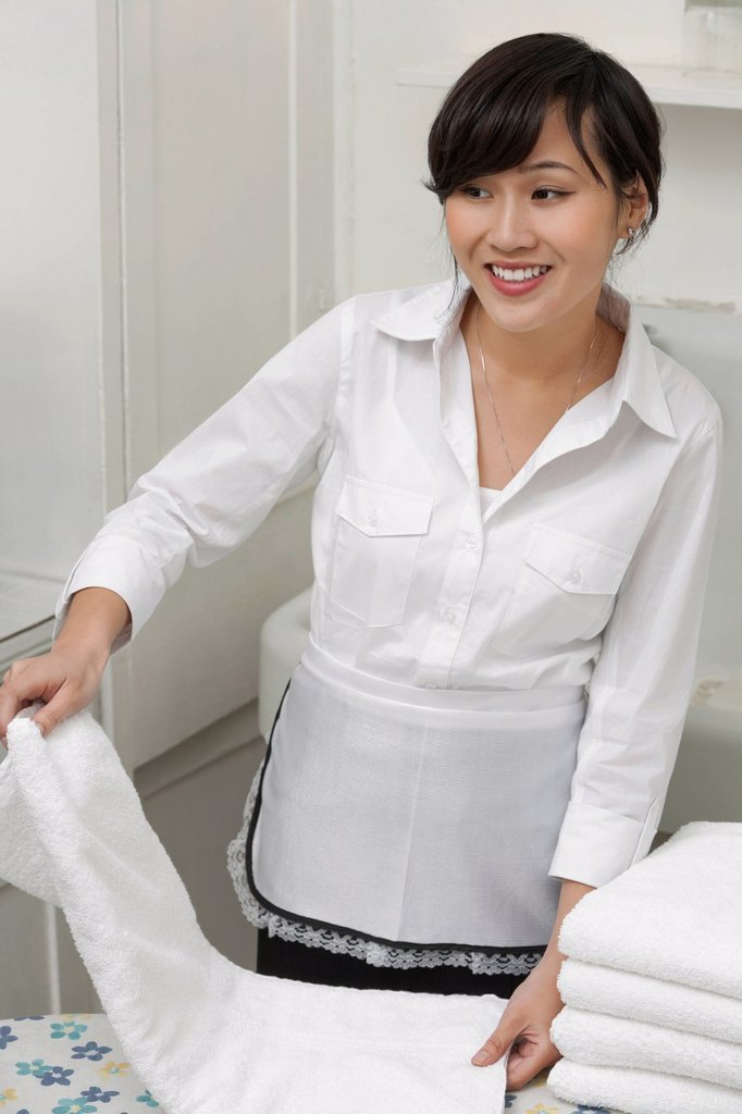 Female housekeeper looking away while folding white towel : Stock Photo