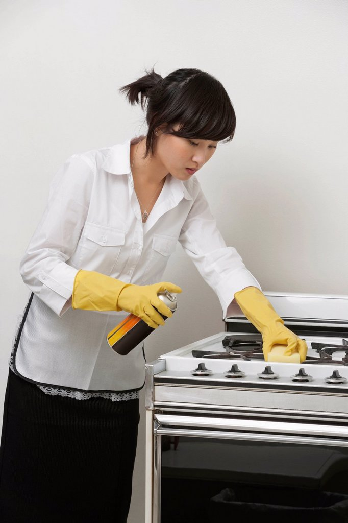 Stock Photo: 1654R-52745 Young maidservant cleaning stove against gray background