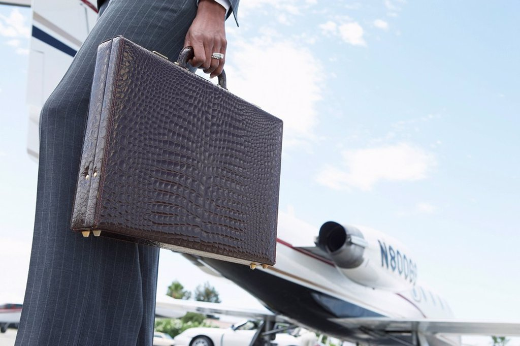 Stock Photo: 1654R-5276 Businesswoman Holding a Briefcase outside of airplane low section