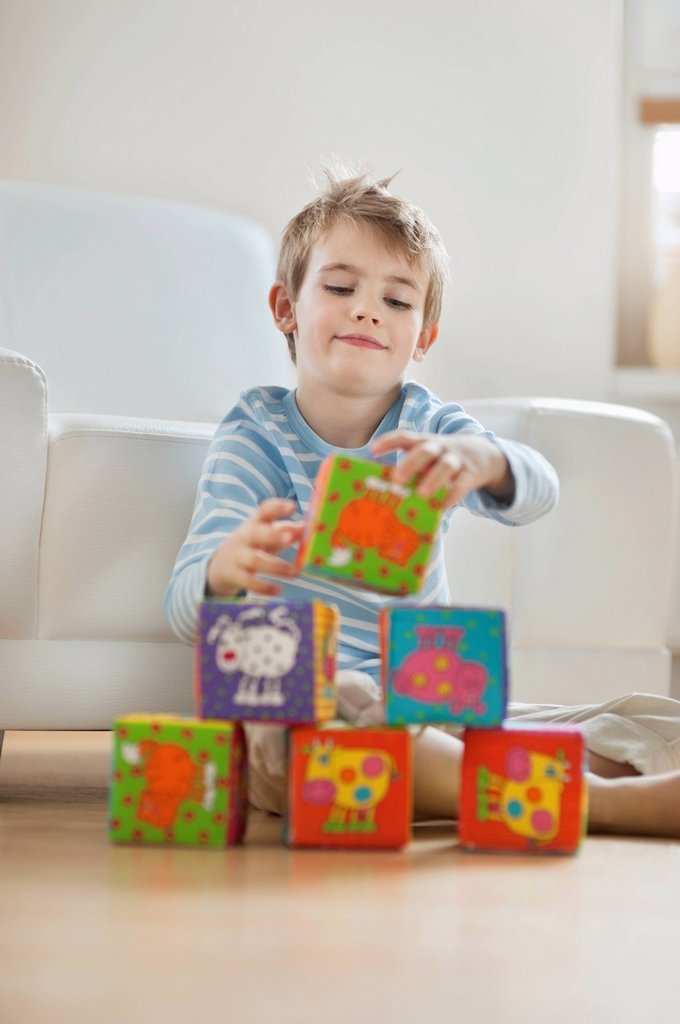 Little boy stacking blocks while sitting on floor : Stock Photo
