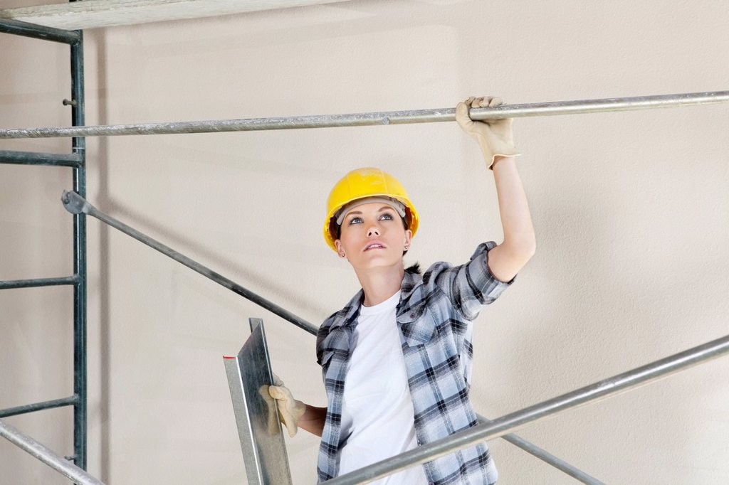 Mid adult female architect looking up while standing under scaffold at construction site : Stock Photo