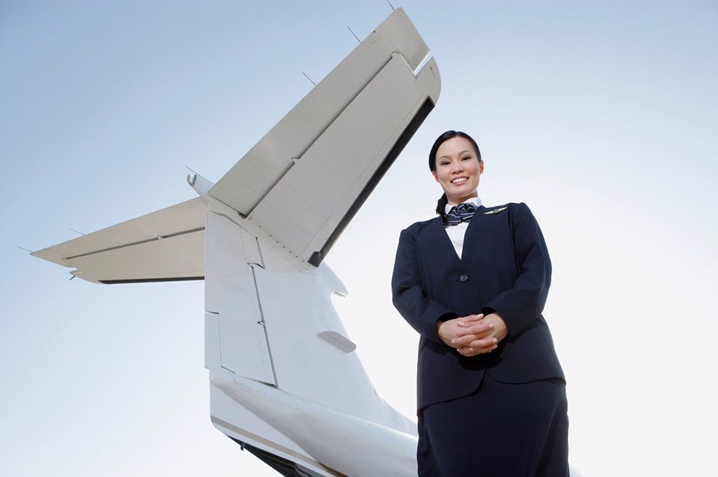 Stewardess in uniform standing below wing of private jet low angle view : Stock Photo