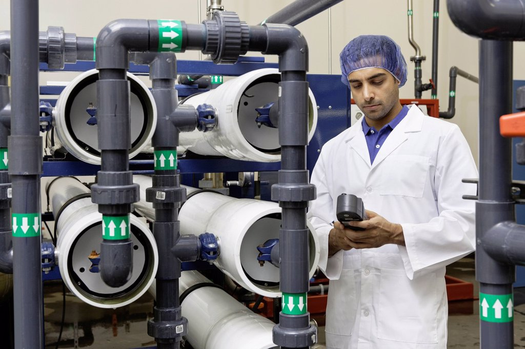 Stock Photo: 1654R-52925 Worker holding an equipment in bottling plant