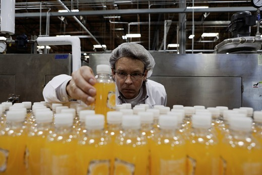 Quality control worker checking juice bottle on production line : Stock Photo