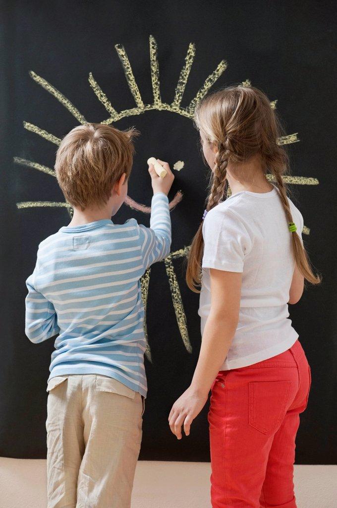 Back view of siblings drawing sun on blackboard : Stock Photo