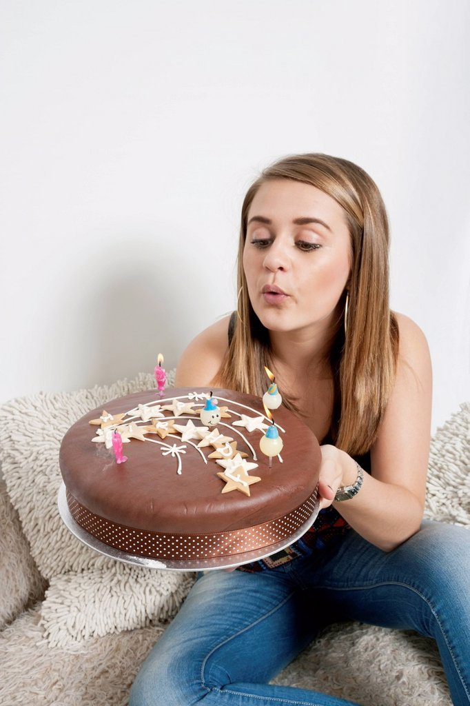 Young woman blowing out candles on birthday cake : Stock Photo