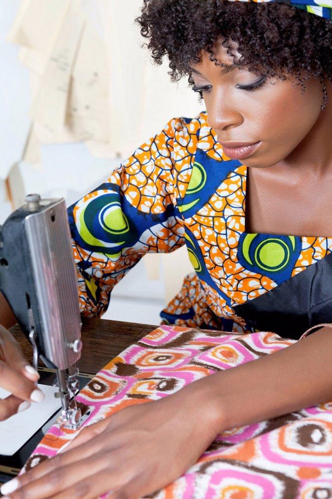 Stock Photo: 1654R-52992 African American female tailor stitching patterned cloth on sewing machine