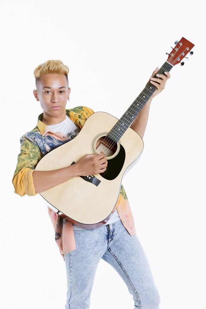 Stock Photo: 1654R-52995 Portrait of a teenage boy playing guitar over gray background