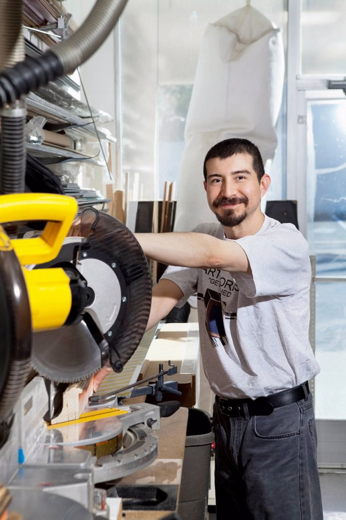 Portrait of a Hispanic employee using circular saw : Stock Photo