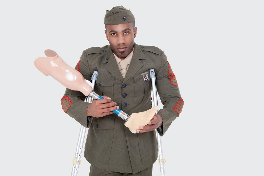 Stock Photo: 1654R-53116 Portrait of a disabled US military officer holding prosthesis leg over gray background