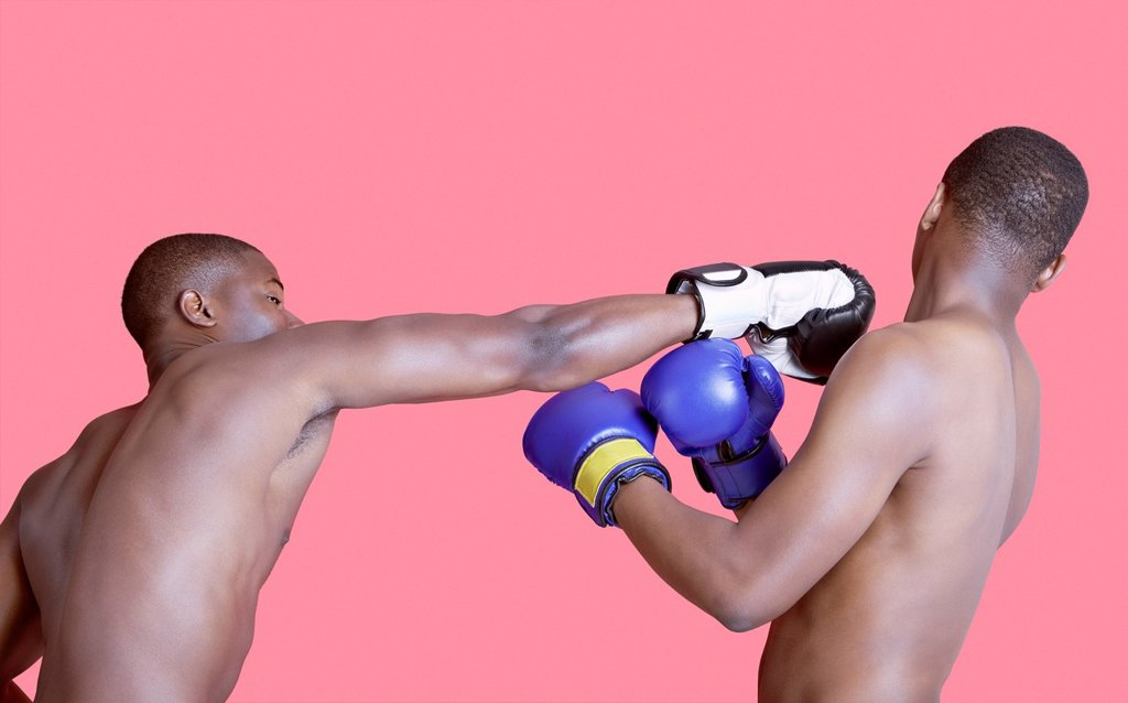 African American boxer punching opponent over pink background : Stock Photo