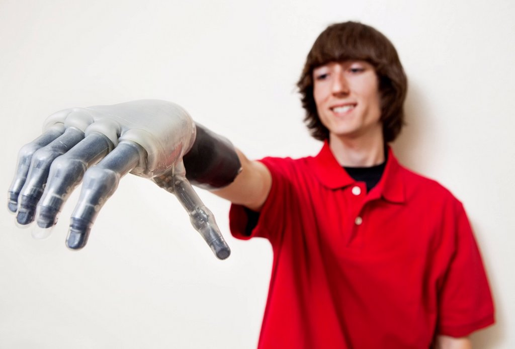 Young man looking at his prosthetic hand over gray background : Stock Photo