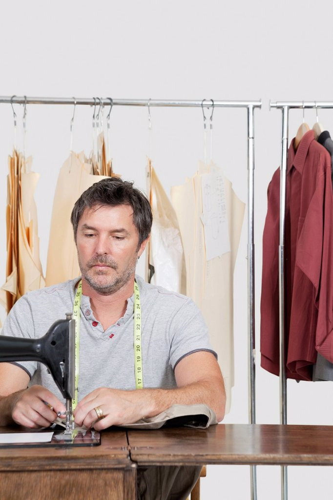 Male dressmaker stitching cloth on sewing machine with clothes rack in background : Stock Photo
