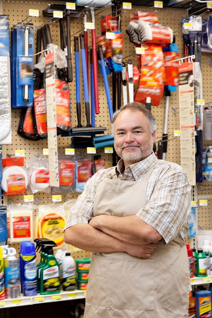 Portrait of a confident mature salesperson with arms crossed in hardware store : Stock Photo