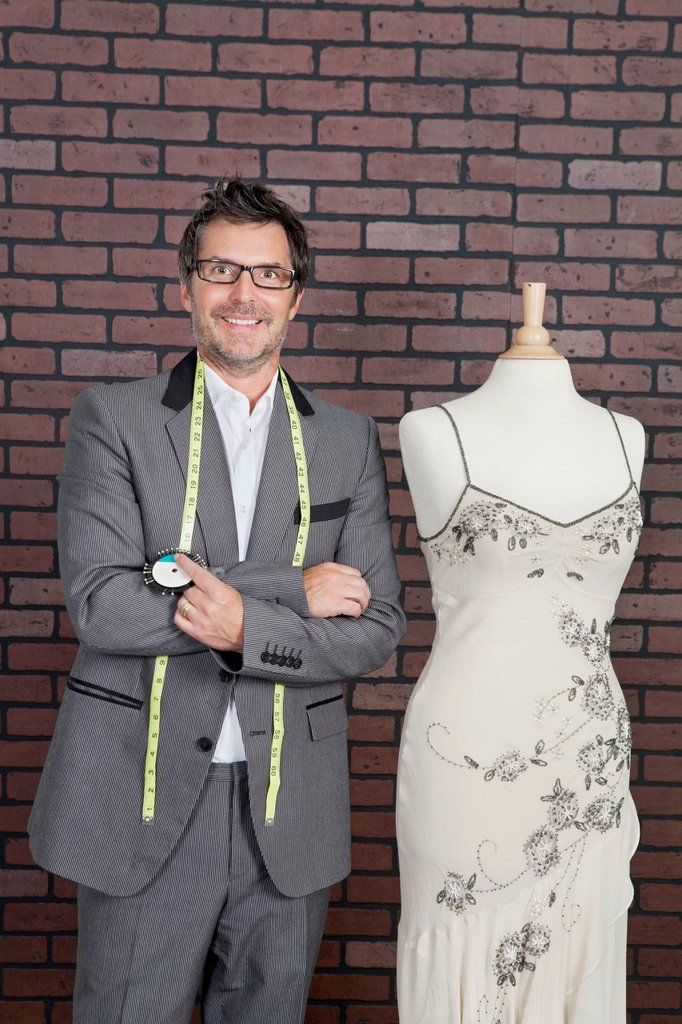 Stock Photo: 1654R-53328 Portrait of mature male fashion designer standing next to tailor´s dummy