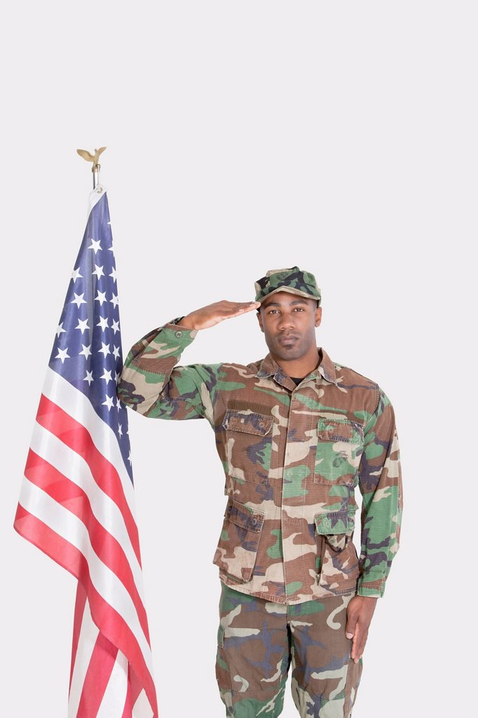 Portrait of US Marine Corps soldier saluting American flag over gray background : Stock Photo