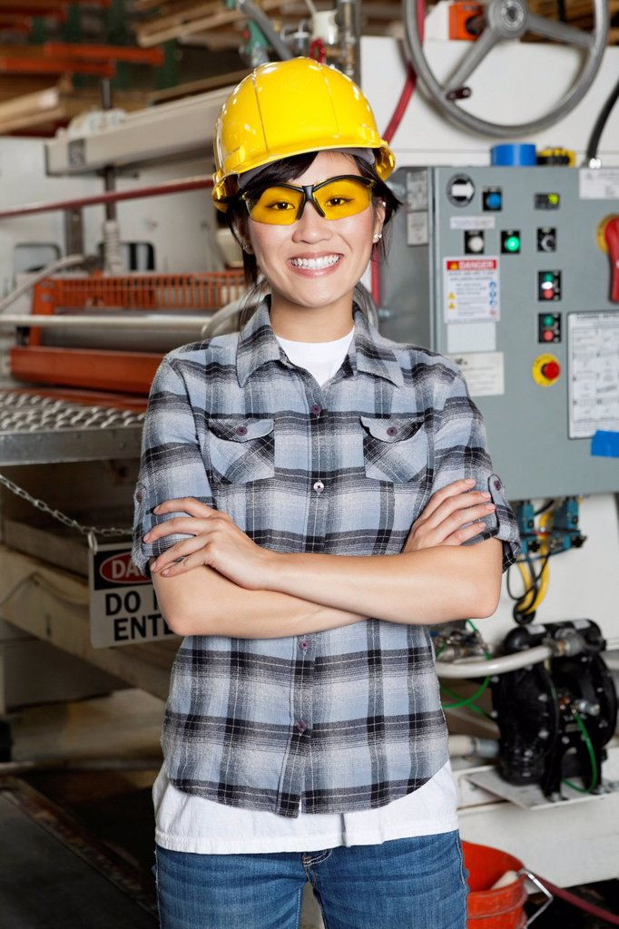Stock Photo: 1654R-53499 Portrait of happy Asian female industrial worker with machinery in background