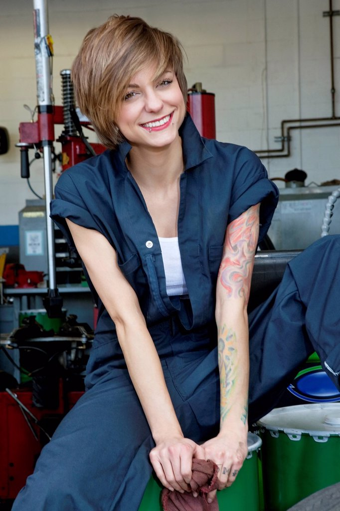 Stock Photo: 1654R-53523 Portrait of a happy young female mechanic sitting on oil drum in car workshop