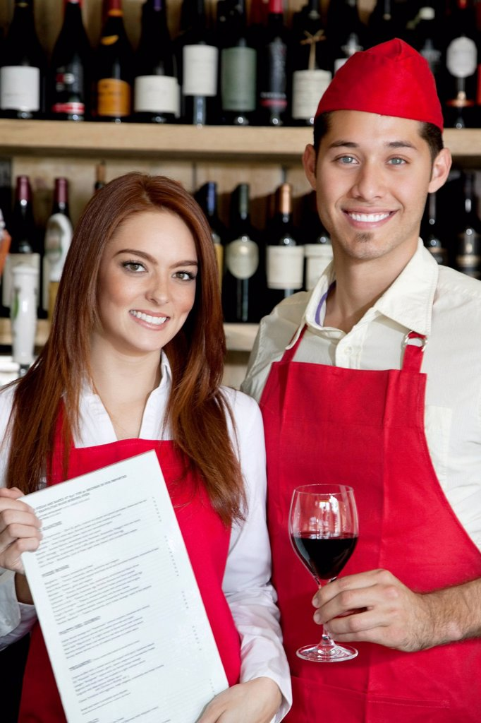 Stock Photo: 1654R-53584 Portrait of young wait staff with wine glass and menu card in bar