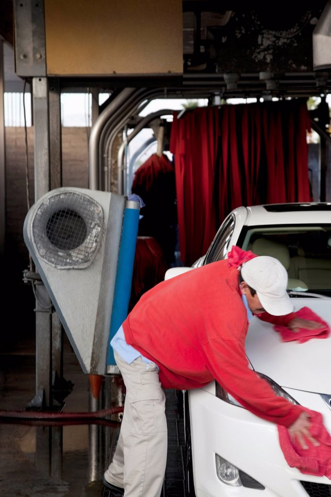 Employee wiping vehicle after washing in car wash : Stock Photo