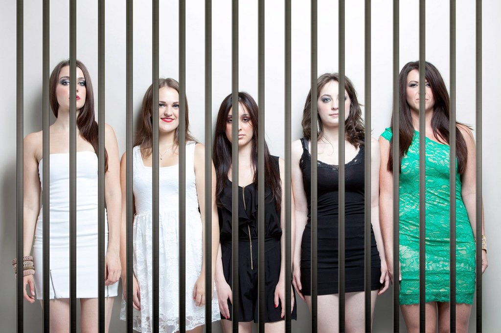 Stock Photo: 1654R-54525 Portrait of five young women standing side by side behinds prison bars