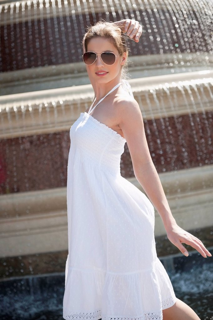 Stock Photo: 1654R-54558 Side view of happy young woman in white halter neck dress standing by water fountain