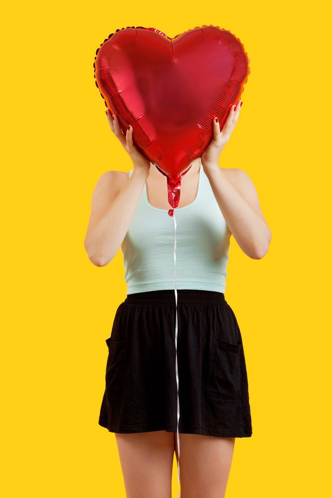 Young woman hiding behind heart shaped balloon over yellow background : Stock Photo
