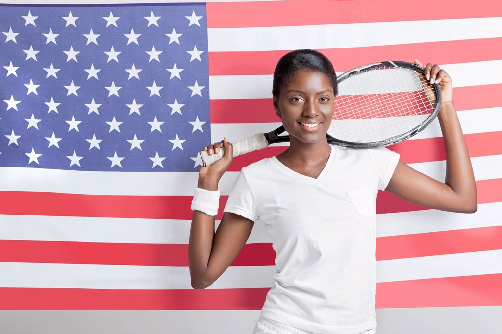 Portrait of young woman with tennis racket against American flag : Stock Photo