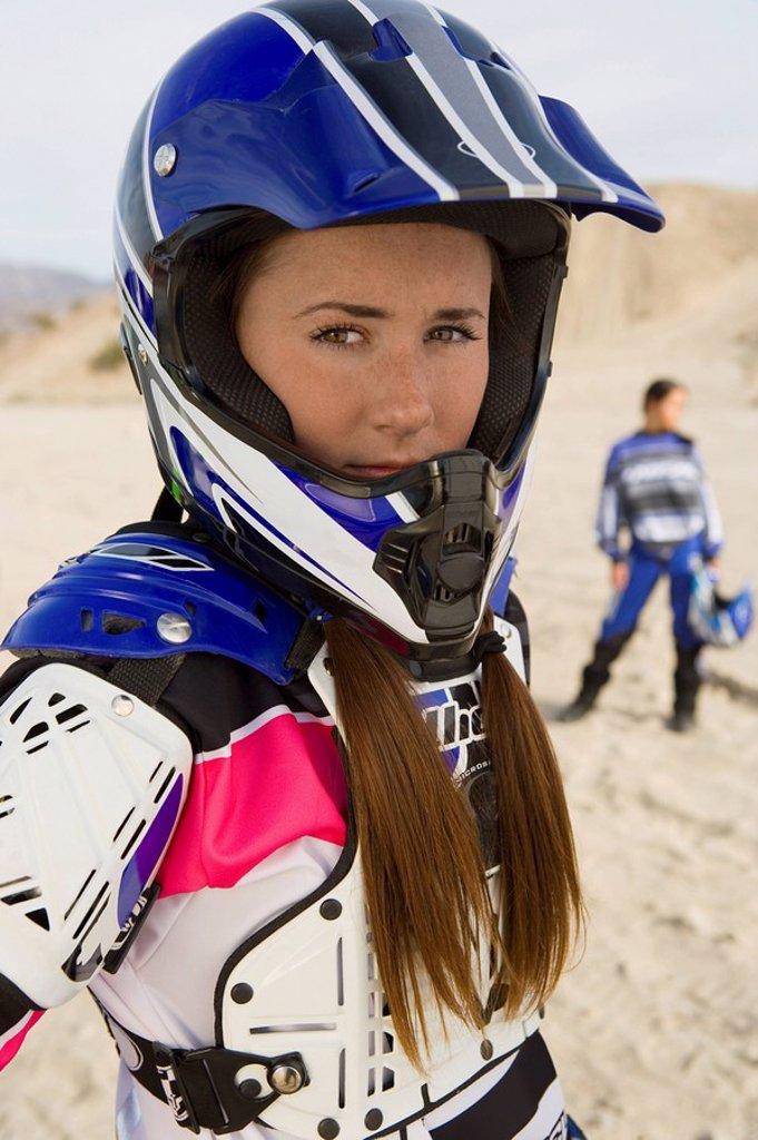 Stock Photo: 1654R-5464 Female motocross racer wearing helmet outdoors portrait