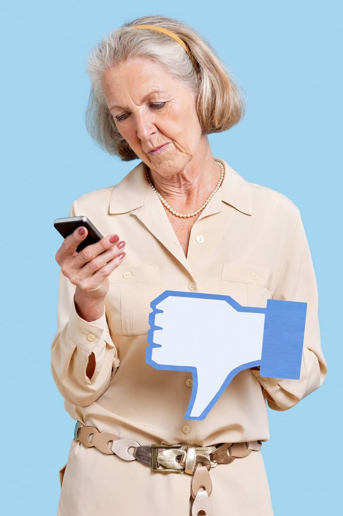Senior woman with cell phone holding fake dislike button against blue background : Stock Photo