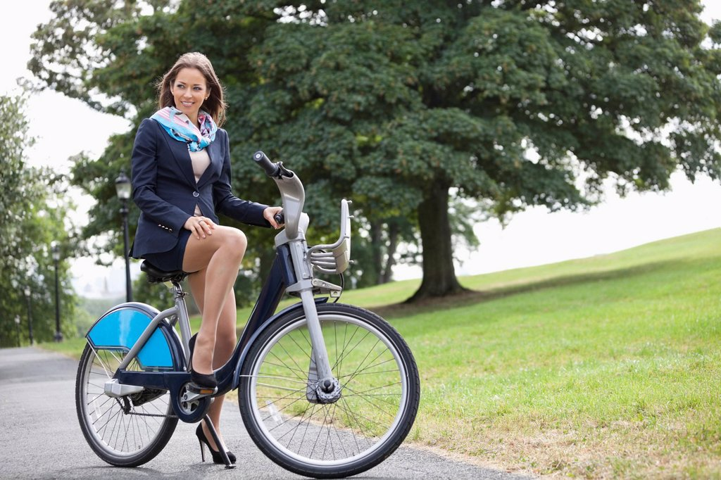 Young businessman riding bicycle while commuting to work : Stock Photo