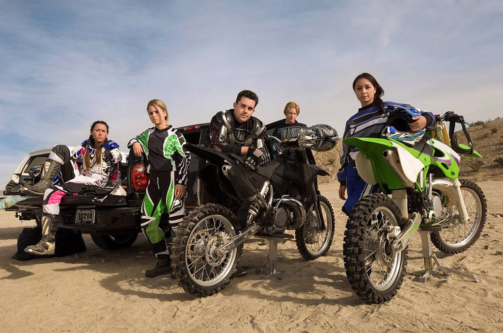 Stock Photo: 1654R-5481 Motocross racers with bikes in desert portrait