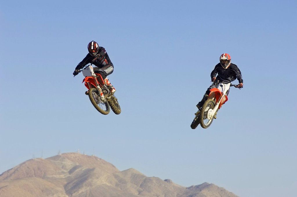 Stock Photo: 1654R-5489 Two motocross Racers in mid_air