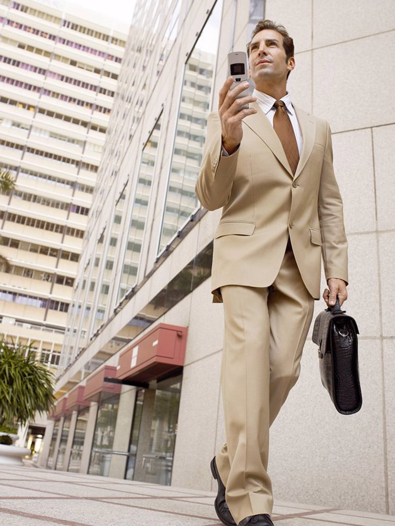 Businessman using mobile phone outside office building : Stock Photo