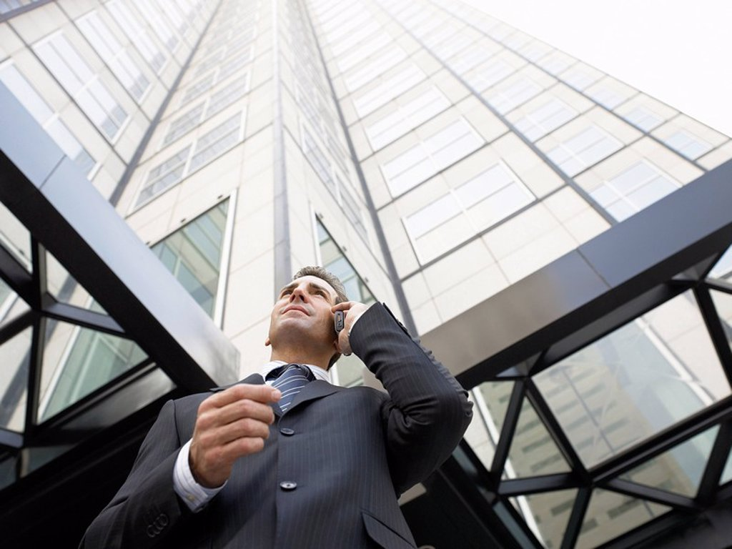 Stock Photo: 1654R-5556 Businessman using mobile phone outside office low angle view