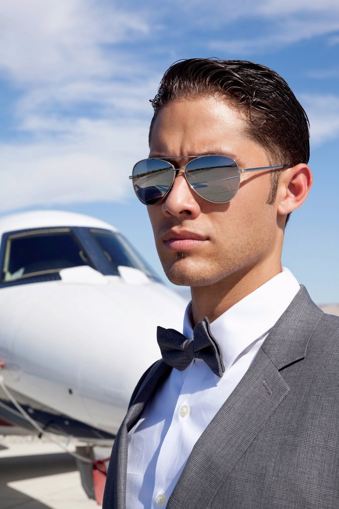 Handsome young men wearing sunglasses with private plane in background : Stock Photo