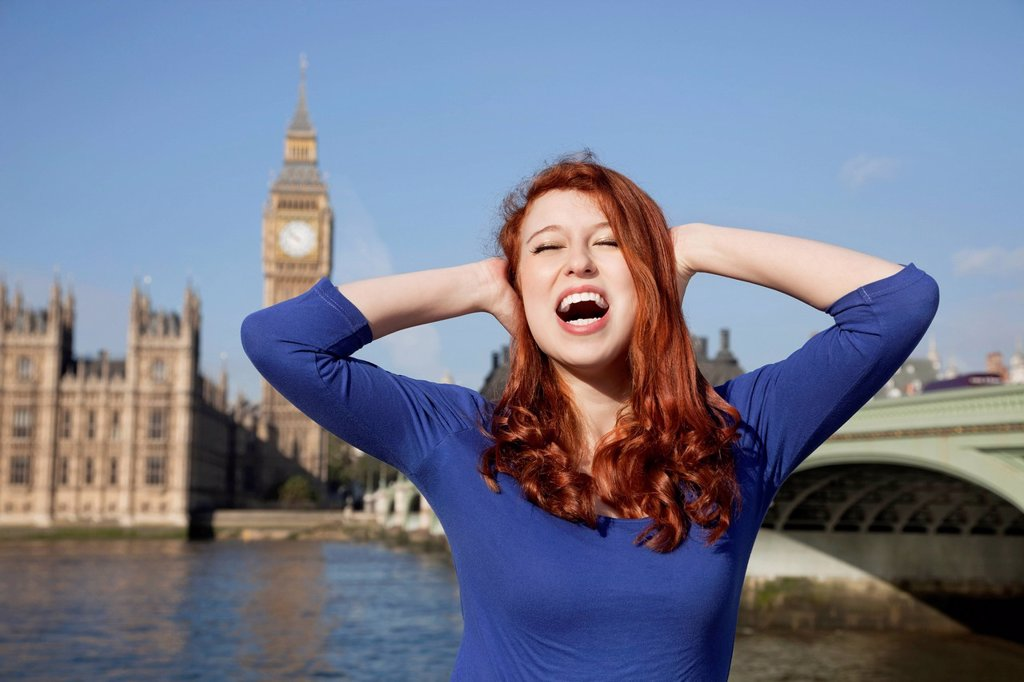 Stock Photo: 1654R-55690 Angry young woman with hands on head screaming against Big Ben clock tower, London, UK