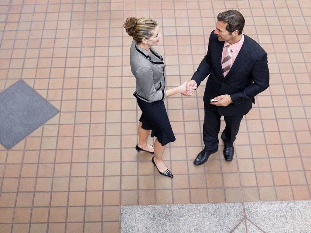 Stock Photo: 1654R-5574 Businesspeople shaking hands indoors elevated view