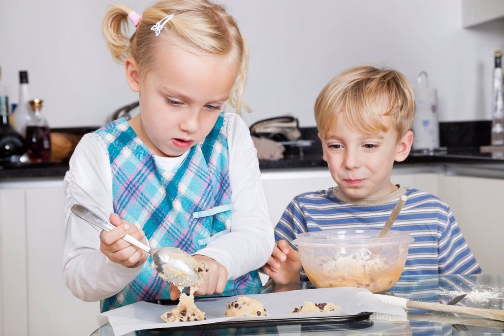Stock Photo: 1654R-55856 Happy brother and sister baking cookies in kitchen
