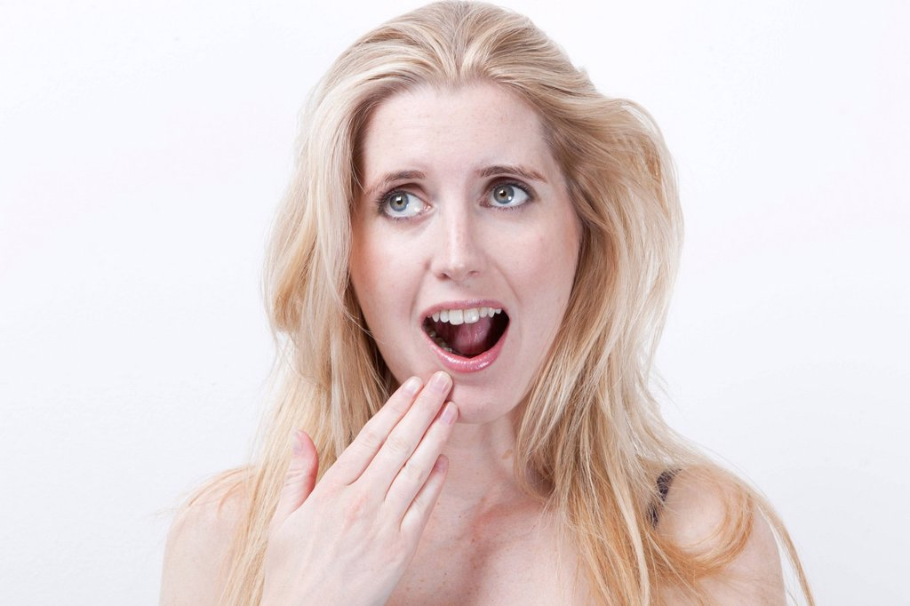 Stock Photo: 1654R-55897 Surprised young woman with mouth open against white background