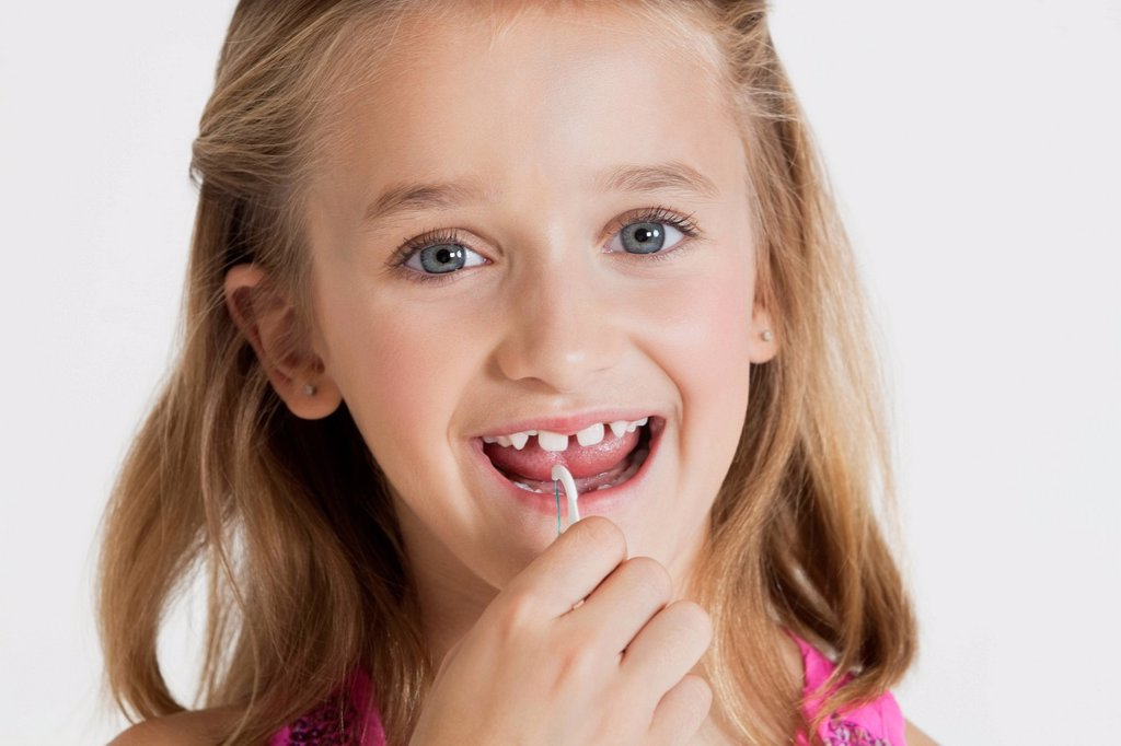 Portrait of young girl flossing teeth against gray background : Stock Photo