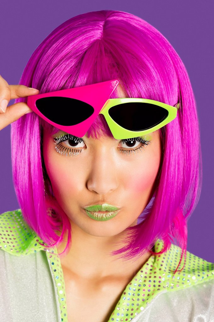 Portrait of young funky woman in pink wig puckering lips over purple background : Stock Photo