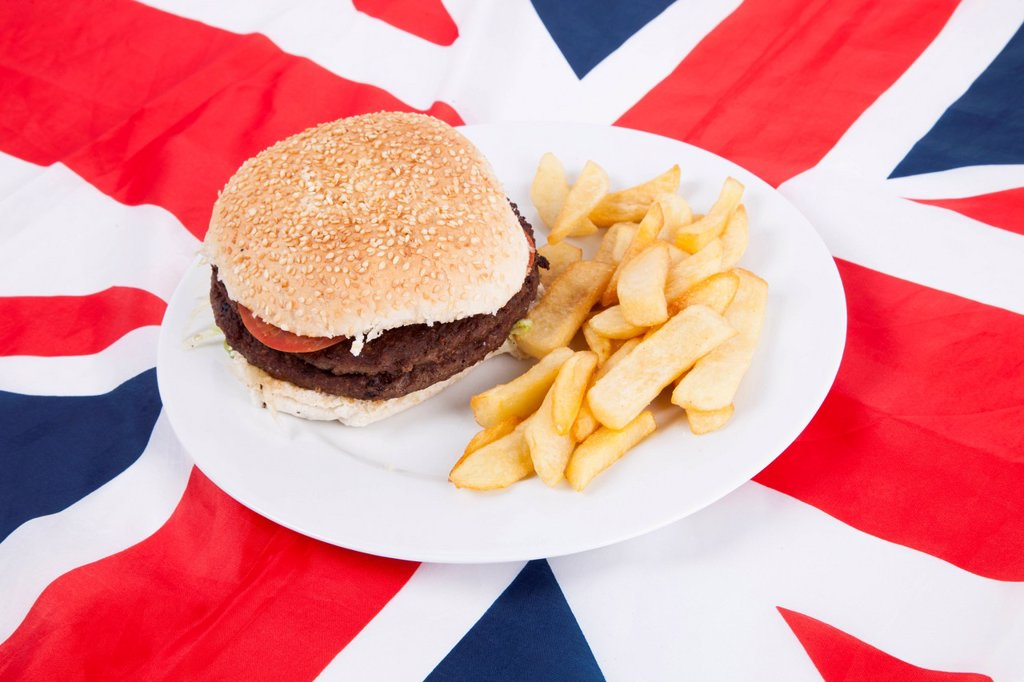 Stock Photo: 1654R-57311 Close_up of hamburger and chips over British flag
