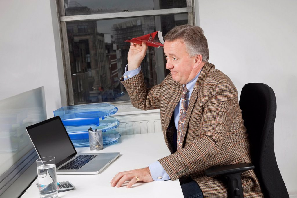 Side view of middle_aged businessman throwing paper airplane in office : Stock Photo